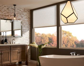 bathroom with large windows and free standing tub